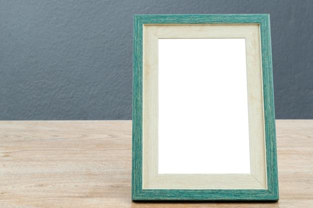 Cadre photo en bois sur table avec fond de texture béton mur gris.