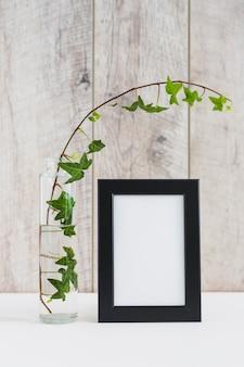Cadre photo avec bordure noire et vase avec lierre sur bureau blanc