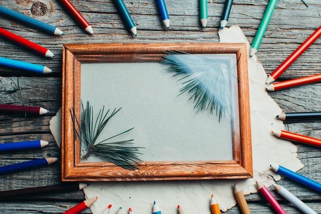 Cadre photo de composition de noël sur la table en bois avec des branches d'arbres avec des crayons