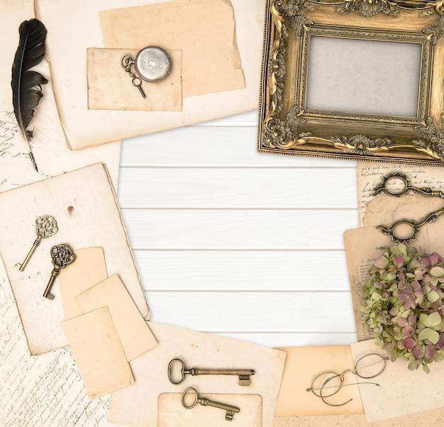 Cadre photo doré antique et papier usagé sur fond de bois