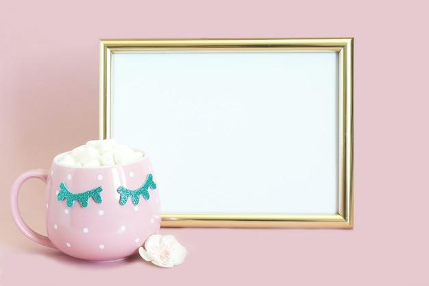 Cadre photo doré et à côté de celui-ci, une tasse à pois rose avec café et guimauves avec des cils fermés bleus brillants.