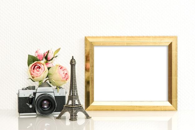 Cadre photo doré, fleurs roses et appareil photo vintage. concept de voyage parisien
