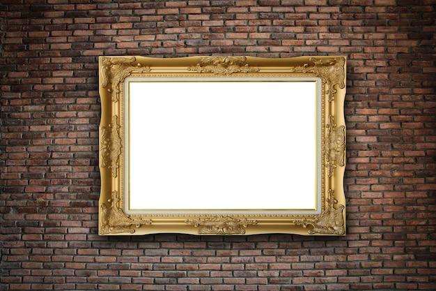 Cadre photo doré vide sur fond de mur de briques.