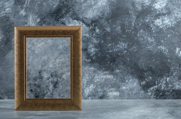 Cadre photo doré vide sur marbre.