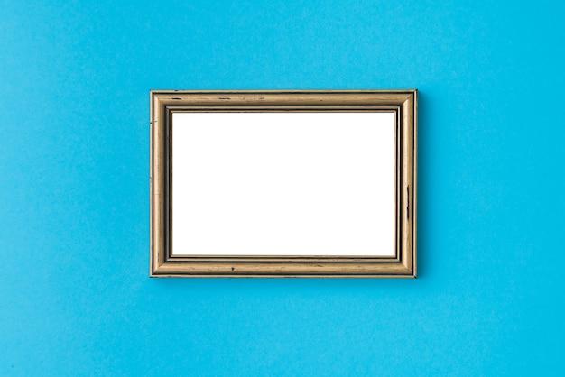 Cadre photo doré vide sur une surface bleue.