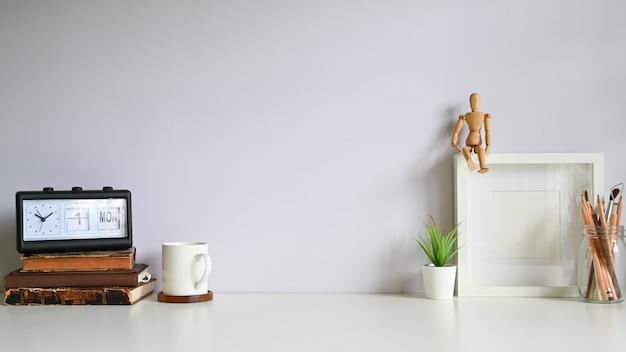 Cadre photo espace de travail, café, alarme, livres avec plante décorer sur une table blanche.