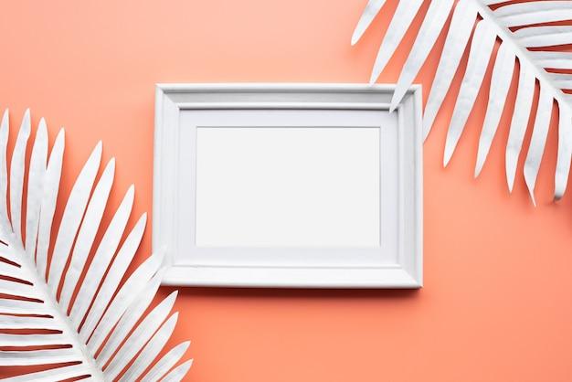 Cadre photo avec feuille tropicale blanche