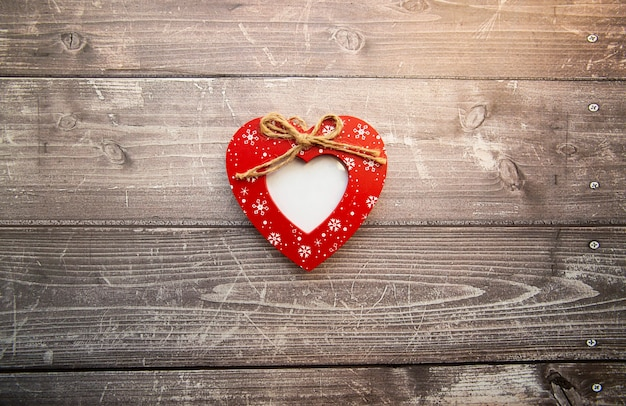 Cadre photo en forme de coeur rouge sur fond de bois