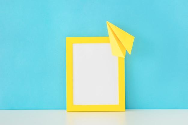 Cadre photo jaune et avion en papier devant le mur bleu