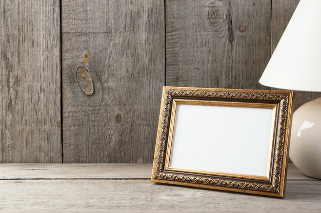 Cadre photo en laiton vide sur fond en bois.