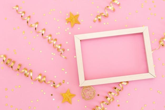 Cadre photo maquette avec un espace pour le texte, confettis de paillettes d'or sur fond rose.