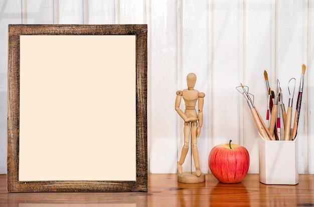 Cadre photo maquette avec poupée en bois, pomme rouge et boîte de pinceaux