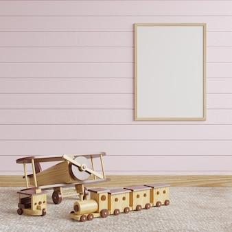 Cadre photo sur un mur en bois rose dans la chambre des enfants avec des jouets en bois