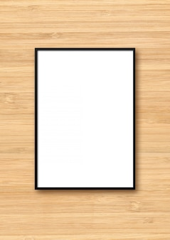 Cadre photo noir accroché à un mur en bois clair