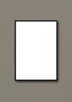 Cadre photo noir accroché à un mur gris foncé.
