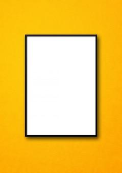 Cadre photo noir accroché à un mur jaune. modèle de maquette vierge