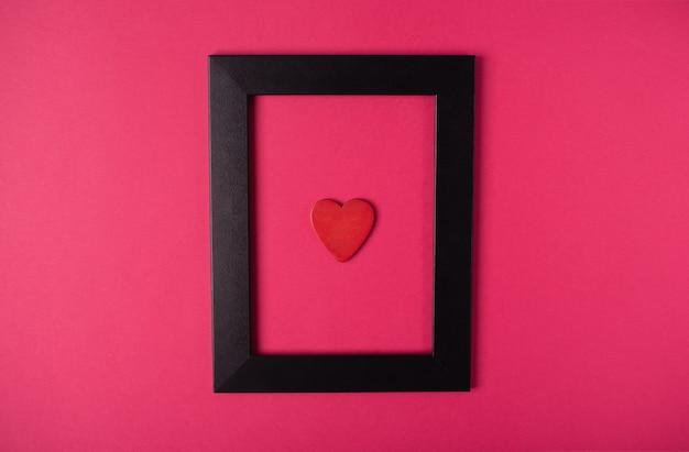 Cadre photo noir avec un coeur rouge à l'intérieur sur le fond rose chaud. concept de la saint-valentin. mise à plat, vue de dessus.