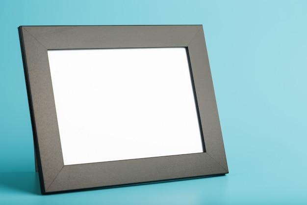 Cadre photo noir avec espace libre sur fond bleu.