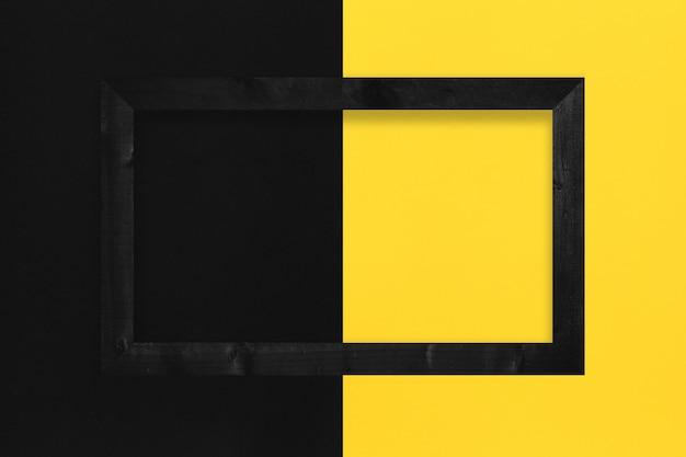 Cadre photo noir placé sur fond de papier jaune et noir et espace de copie.