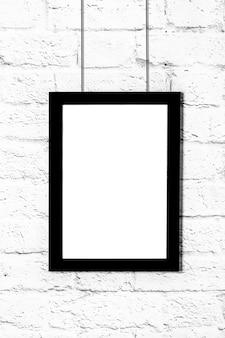 Cadre photo noir vertical accroché sur un mur de briques. maquette avec espace de copie.