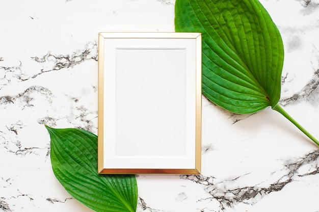 Cadre photo en or avec des feuilles tropicales sur fond de marbre. cadre maquette