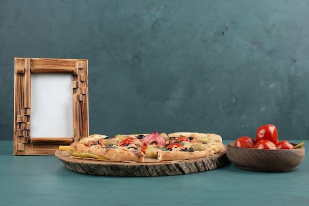 Cadre photo, pizza et bol de tomates marinées sur table bleue.