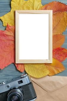 Cadre photo avec une place pour l'espace de copie à côté de feuilles sèches et un appareil photo vintage.
