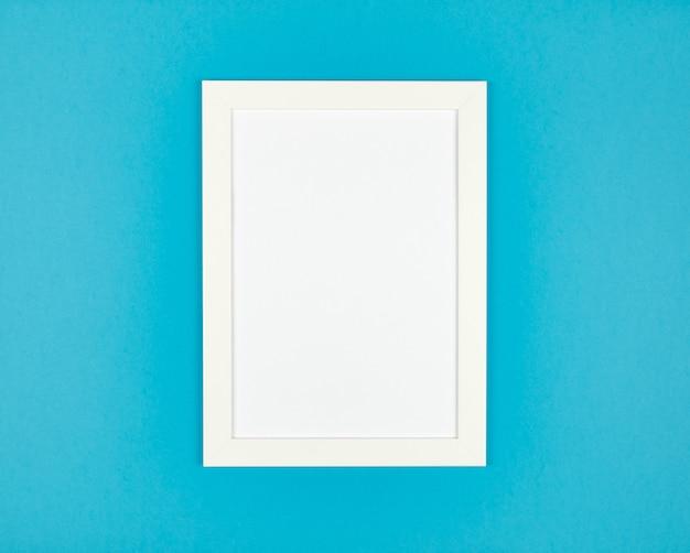 Cadre photo à plat sur fond de papier bleu pastel texturé