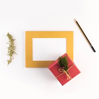 Cadre photo près de la boîte, du crayon et du rameau de conifères
