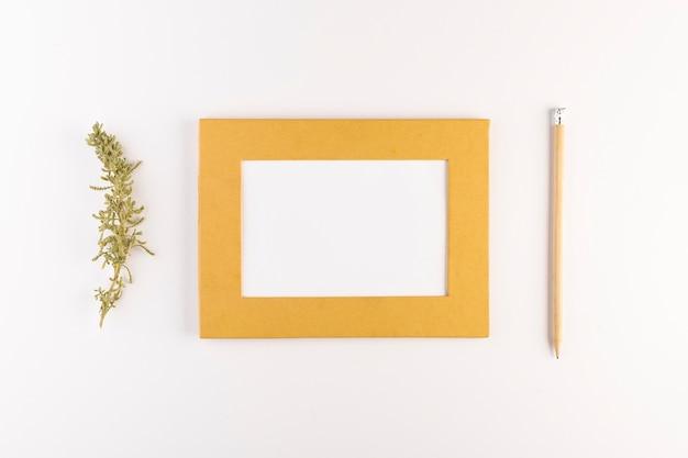 Cadre photo près d'un crayon et d'un rameau de conifères