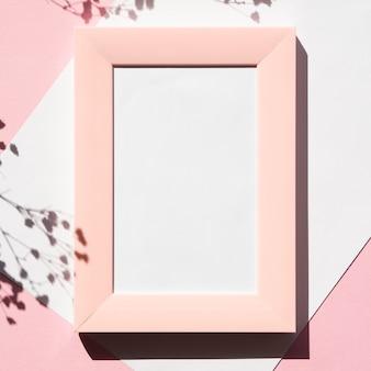 Cadre photo rose sur un blanc vierge avec une ombre de branche sur un fond rose