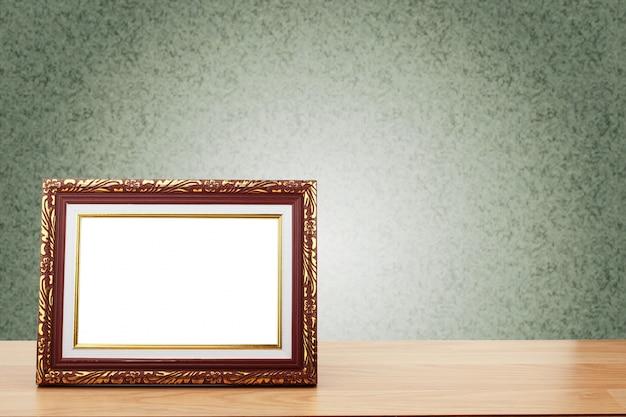 Cadre photo sur une table en bois sur fond de mur végétalisé