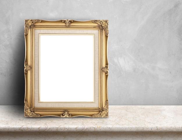 Cadre photo victorien or blanc sur une table de marbre crème au mur de béton gris