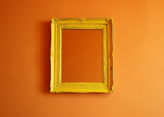 Cadre photo vide antique jaune sur fond de mur orange