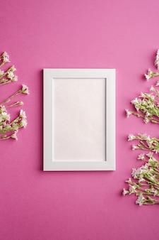 Cadre photo vide blanc avec des fleurs de mouron des oreilles de souris sur fond rose violet, vue de dessus copie espace
