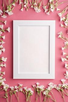 Cadre photo vide blanc avec des fleurs de mouron des oreilles de souris sur la table rose pourpre, vue de dessus copie espace