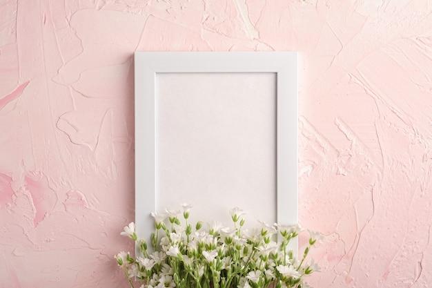 Cadre photo vide blanc avec des fleurs de mouron des oreilles de souris sur table texturée rose, vue de dessus copie espace