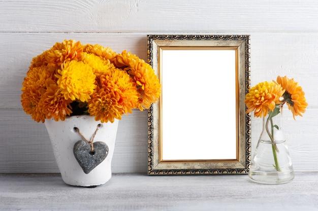 Cadre photo vide et fleurs de chrysanthème orange sur table rustique blanche