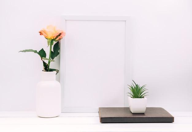 Cadre photo vide; journal intime; plante avec rose sur table blanche