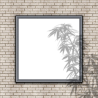 Cadre photo vide sur mur de briques avec superposition d'ombre de plante