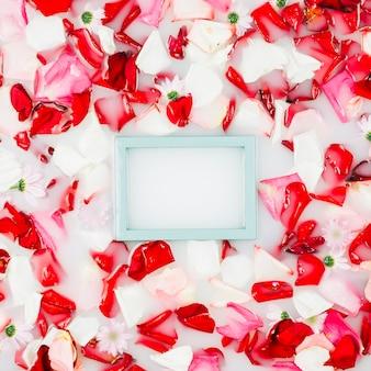 Cadre photo vide avec des pétales de fleurs flottant sur l'eau