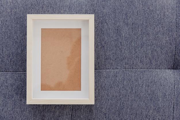 Cadre photo vide place sur un tissu en tissu bleu.