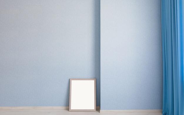 Cadre photo vide sur le sol, s'appuyant sur le mur bleu du salon avec rideaux et parquet en bois.