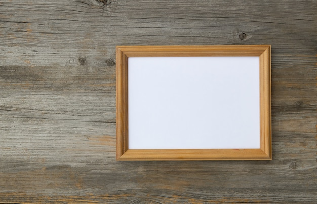 Cadre photo vide sur une table en bois clair, maquette pour ajouter votre photo à l'espace de copie.