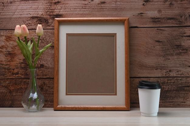 Cadre photo vide, tasse à café et pot de fleurs sur table blanche et mur en bois.