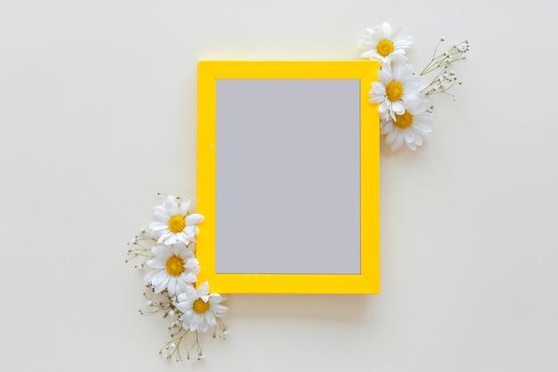 Cadre photo vide avec vase à fleur devant un fond blanc