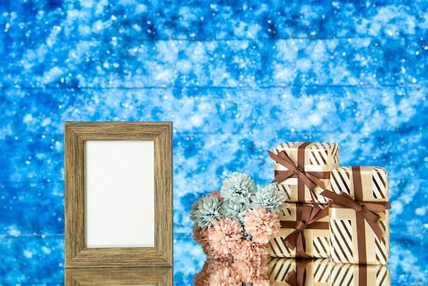 Le cadre photo vide de vue de face présente des fleurs sur l'espace libre de fond abstrait bleu
