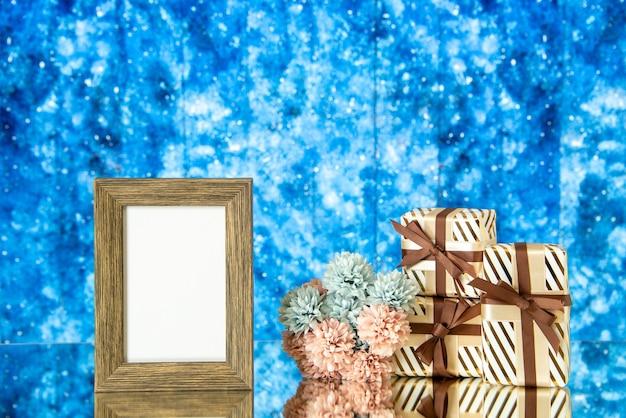 Le cadre photo vide vue de face présente des fleurs sur fond abstrait bleu