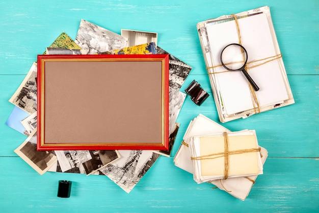 Cadre photo et vieilles photos dans une pile sur table bleue, mise à plat
