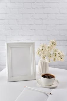 Cadre photo vierge, agenda, cahier, crayon, vase avec des fleurs et une tasse de café.